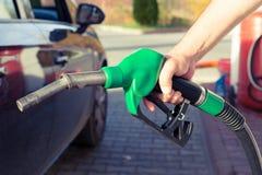 Equipaggi la pompa di benzina della tenuta della mano in una stazione di servizio immagine stock