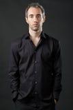 Equipaggi la posizione in camicia nera su priorità bassa scura. Immagine Stock