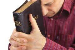 Uomo che prega tenendo la bibbia Immagini Stock Libere da Diritti