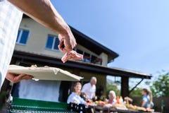 Equipaggi la preparazione la carne alla griglia all'aperto e della famiglia che si siede alla tavola all'aperto Fotografie Stock Libere da Diritti