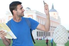 Equipaggi la presa del selfie di divertimento davanti a costruzione classica mentre tengono una mappa Immagine Stock