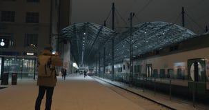 Equipaggi la presa del video mobile del treno che lascia la stazione alla notte, Helsinki stock footage
