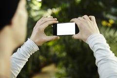 Equipaggi la presa dell'immagine della foto dal telefono cellulare in un viaggio di viaggio Lo schermo in bianco per la disposizi Fotografie Stock