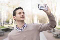 Equipaggi la presa dell'immagine di se stesso con lo smartphone, all'aperto. Immagini Stock