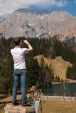 Equipaggi la presa della foto di piccolo lago mountain sullo Smart Phone in alpi Immagini Stock
