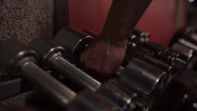 Equipaggi la presa delle teste di legno dallo scaffale di stoccaggio in palestra video d archivio