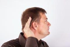 Equipaggi la protesi acustica d'uso che foggia a coppa la sua mano dietro l'orecchio immagini stock