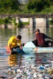 Equipaggi la pulitura fuori della sua benna in fiume inquinante Immagine Stock Libera da Diritti