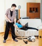 Equipaggi la pulizia con il pulitore durante la donna sopra il sofà immagini stock libere da diritti