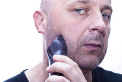 Equipaggi la rasatura della sua barba fuori con un rasoio elettrico Fotografia Stock Libera da Diritti