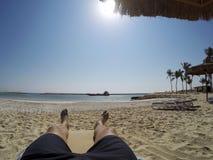 Equipaggi la refrigerazione alle gambe ed al piede della spiaggia nella baia dell'Oman Salalah Souly fotografia stock libera da diritti