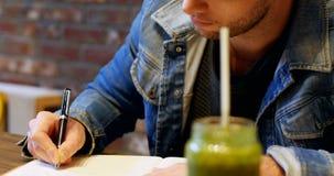 Equipaggi la scrittura nella sua latteria con succo sulla tavola video d archivio