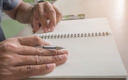 Equipaggi la scrittura sul taccuino e sullo Smart Phone sul DES Fotografia Stock