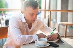 Equipaggi la scrittura sul taccuino o sul pianificatore con lo smartphone ed il caffè al caffè all'aperto Fotografia Stock Libera da Diritti