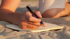 Equipaggi la scrittura in suo diario alla spiaggia stock footage