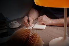 Equipaggi la scrittura in un taccuino su una tavola di legno fotografie stock libere da diritti