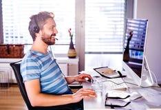 Equipaggi la seduta allo scrittorio che funziona dalla casa sul computer Immagine Stock