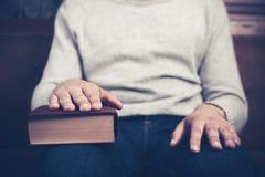 Equipaggi la seduta con la sua mano su un libro Immagine Stock