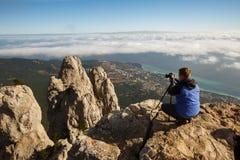 Equipaggi la seduta con una macchina fotografica della foto e del treppiede su un picco di alta montagna sopra le nuvole, la citt Fotografie Stock