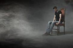 Equipaggi la seduta e pensi su una sedia Immagini Stock Libere da Diritti