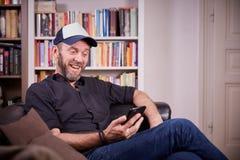 Equipaggi la seduta nel suo salone con la risata del telefono cellulare Fotografie Stock