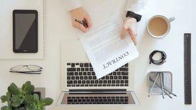 Equipaggi la seduta nell'ufficio che lavora al progetto sul computer portatile, firmi il contratto stock footage