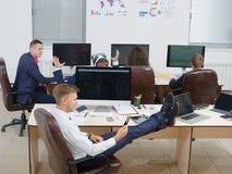 Equipaggi la seduta nell'ufficio con le gambe sulla tavola immagini stock libere da diritti