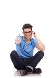 Equipaggi la seduta, pollici in su, sul telefono Immagini Stock