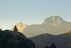 Equipaggi la seduta su una scogliera al tramonto circondata dalle montagne Immagine Stock