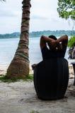 Equipaggi la seduta su una sedia che si rilassa alla spiaggia Immagini Stock