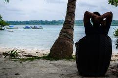 Equipaggi la seduta su una sedia che si rilassa alla spiaggia Fotografie Stock