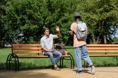 Equipaggi la seduta sul banco e l'ondeggiamento all'amico in parco Immagine Stock