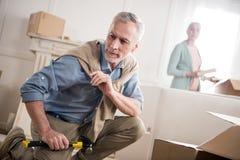 Equipaggi la seduta sul pavimento con il martello a disposizione con la moglie dietro fotografia stock libera da diritti