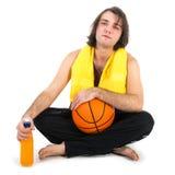 Equipaggi la seduta sul pavimento con pallacanestro e succo d'arancia, isolati a bianco Immagine Stock