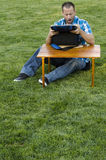 Equipaggi la seduta sull'erba fuori davanti ad una tavola con un dispositivo di raffreddamento Fotografie Stock