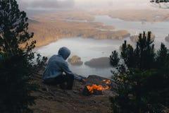 Equipaggi la seduta sull'orlo con fuoco di accampamento sopra la vista costiera con le isole al tramonto Fotografia Stock