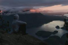 Equipaggi la seduta sull'orlo con fuoco di accampamento sopra la vista costiera con le isole e le foreste in tempo nuvoloso dalla Immagine Stock Libera da Diritti