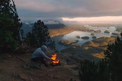 Equipaggi la seduta sull'orlo con fuoco di accampamento sopra la vista costiera con le isole e le foreste in tempo nuvoloso dalla Fotografia Stock Libera da Diritti