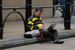 Equipaggi la seduta sulla pavimentazione facendo uso di un computer portatile Fotografia Stock Libera da Diritti