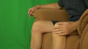 Equipaggi la seduta sulla poltrona e strocking il suo ginocchio dalle mani della palma video d archivio