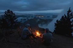 Equipaggi la seduta sulla scogliera con fuoco di accampamento sopra la vista costiera sulla baia nella sera Immagini Stock Libere da Diritti