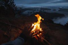 Equipaggi la seduta sulla scogliera con fuoco di accampamento sopra la vista costiera sulla baia nella sera Fotografia Stock Libera da Diritti