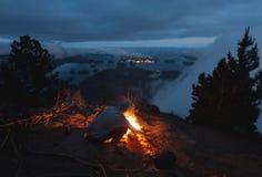 Equipaggi la seduta sulla scogliera con fuoco di accampamento sopra la vista costiera sulla baia nella sera Fotografie Stock