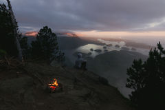 Equipaggi la seduta sulla scogliera con fuoco di accampamento sopra la vista costiera sulla baia nella sera Fotografia Stock