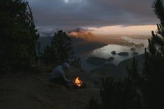Equipaggi la seduta sulla scogliera con fuoco di accampamento sopra la vista costiera sulla baia nella sera Immagine Stock Libera da Diritti