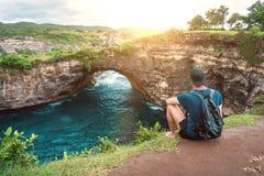 Equipaggi la seduta sulla scogliera e godere di bello paesaggio Spiaggia rotta, Nusa Penida Immagine Stock