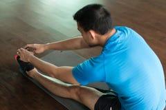 Equipaggi la seduta sulla stuoia di esercizio mentre toccano le sue dita del piede Fotografia Stock Libera da Diritti