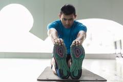 Equipaggi la seduta sulla stuoia di esercizio mentre toccano le sue dita del piede durante l'allungamento Immagini Stock