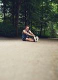Equipaggi la seduta sulla terra ed il raggiungimento delle sue dita del piede Fotografie Stock