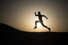 Equipaggi la siluetta corrente al tramonto, giovane caucasian fatto funzionare in montagna fotografia stock libera da diritti